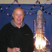 Astronaut Story Musgrave poses in front of the space shuttle ice sculpture graciously donated by Dol